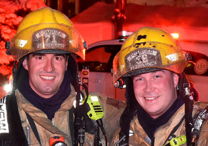 Photograph of two smiling firefighters in firefighting gear, in front of a car, a fire truck and many houses, at night, under the lights.