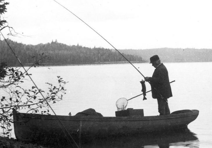 Black and white photo of fishermen in a steamboat on lac Édouard. In the foreground, a boat on the river's edge; in it stands a man unhooking a fish from his rod
