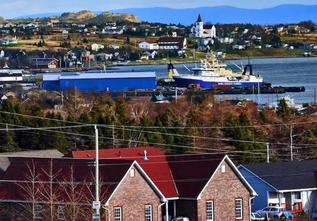 Colour photograph showing a ship in a bay with trees and homes wrapping around the bay in the foreground and background.