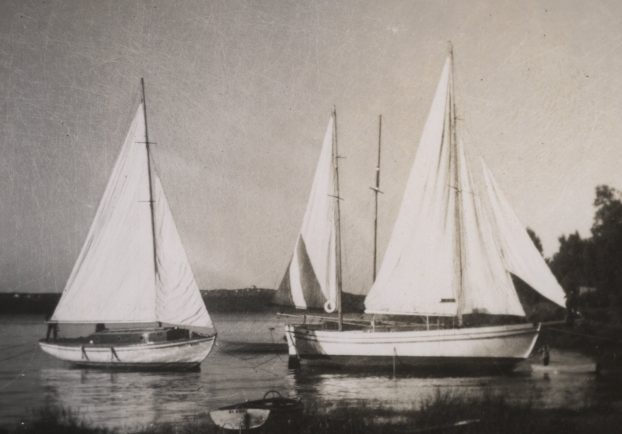 Black and white photograph of three white yachts, with hoisted sails, anchored near the shore.