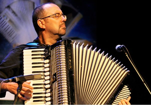 Colour photograph of Martin Bellemare standing and playing piano accordion, as he faces the audience with his eyes closed.