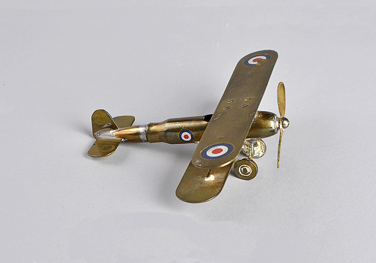A small polished brass plane made from a bullet. It has one propeller in the front and has targets painted on each wing and on the body.