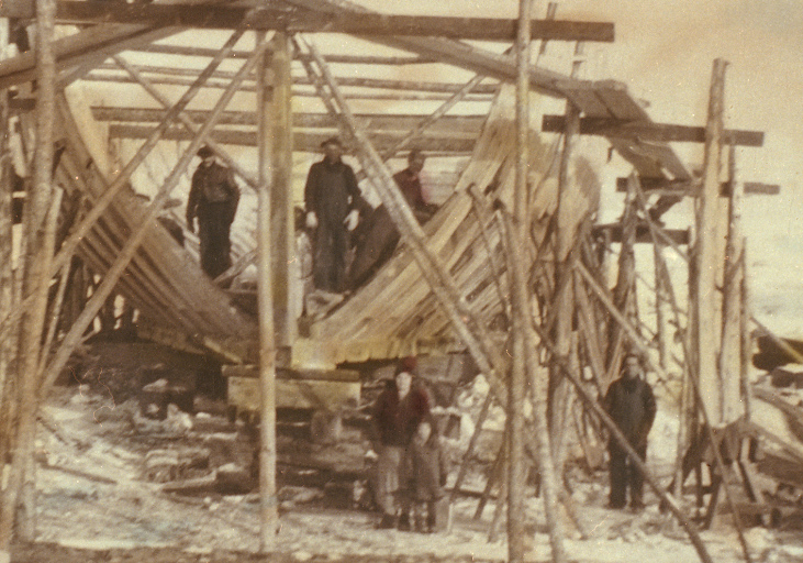 View of a schooner under construction. The structure of the ship is surrounded by scaffolding.