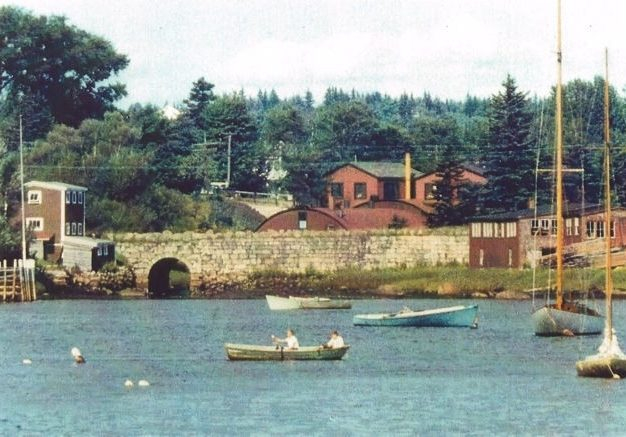 A colour photo with boats in the foreground looking from Mill Cove toward Hawboldt Gas Engines showing the old stone bridge, the red rounded foundry, machine shop and main office.