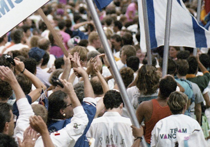 A large, tightly packed crowd of LGBTQ2S+ athletes and allies in B.C. Place Stadium, Vancouver, Canada, wave their arms and flags and sway to music at the Celebration '90 Gay Games III Opening Ceremonies.