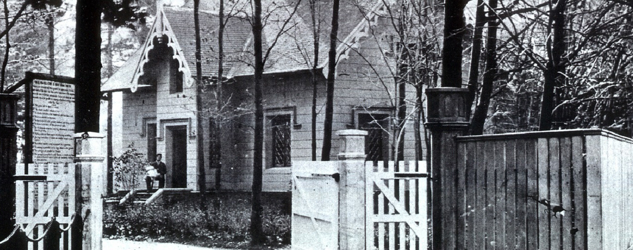 Black and white picture of a house surrounded by trees. A man is sitting on the front step holding a white-clothed baby. A large wood fence with open gates at the forefront.