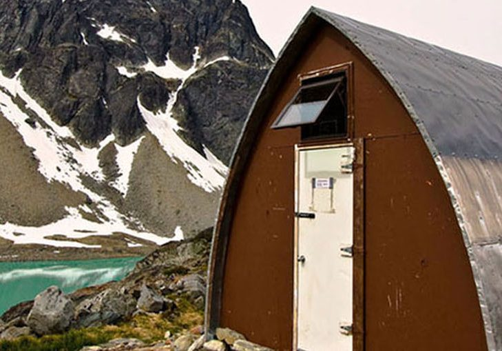 The Gothic Arch Hut front entrance with its brown front end-wall and bright white door sits next to the turquoise water of the glacial lake. A dark peak dotted with snow is visible in the background.