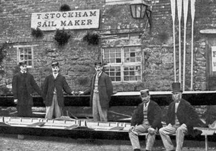 Image of the Paris Crew team members with their manager J. A. Harding posing in front of a boat house upon their arrival in Southampton, England. This black and white photo from July 1867 depicts a building made of stone blocks with their rowing scull positioned in front of the building, with rowing oars propped against its facade.