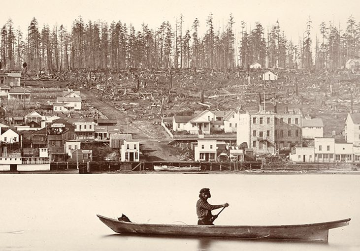 A sepia toned photograph of a man canoeing on the Fraser River in front of a recently deforested New Westminster. New Westminster has multiple buildings along the river, but the buildings become scarcer further up the hill. The upper portion of the hill is littered with tree stumps.