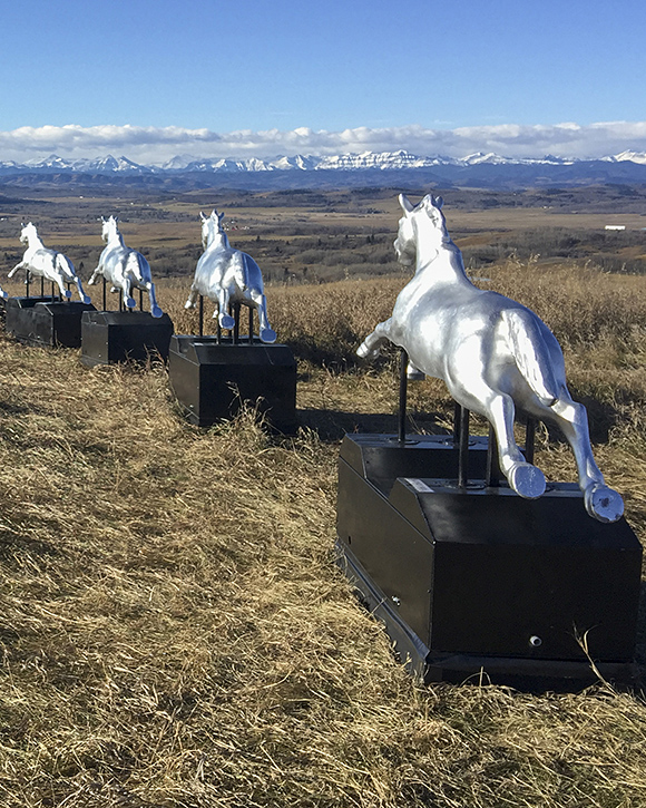 Colour photograph of landscape with eight silver coin-operated horses lined up in front of mountain panorama