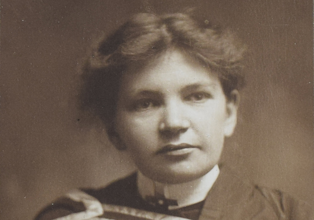 Black and white photograph of Maude Abbott as a young adult, from the waist up. She is wearing a graduation gown. Her dark hair is tied behind her head and she is looking slightly to her left.