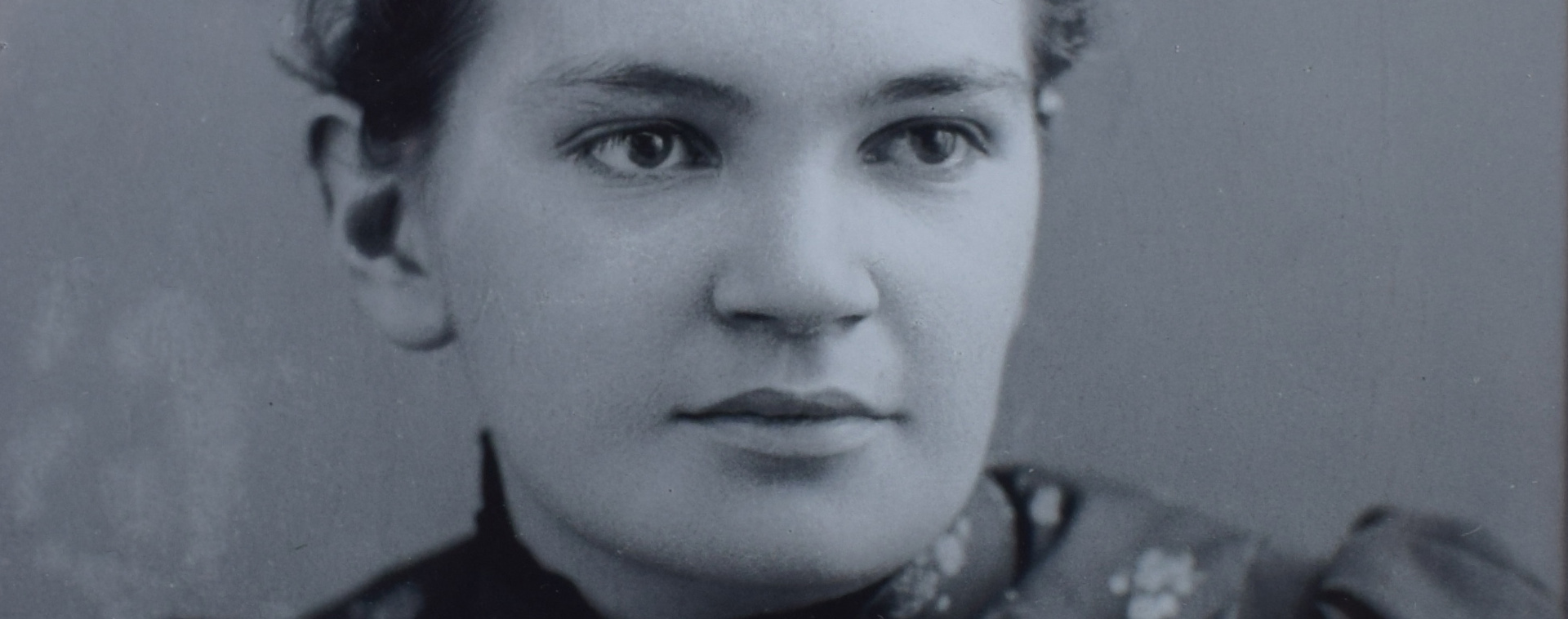 Photograph showing the face of Dr. Maude Elizabeth Abbott in a panoramic close-up. She is young and wears a flowered dress. Her gaze is piercing. She smiles peacefully. She is 22 years old.