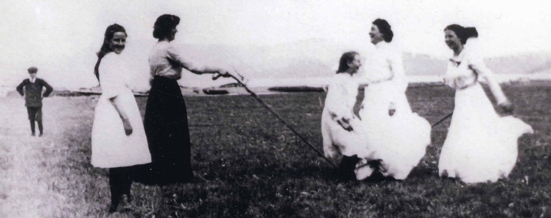 A black and white photograph of women skipping with a jump rope in a field.